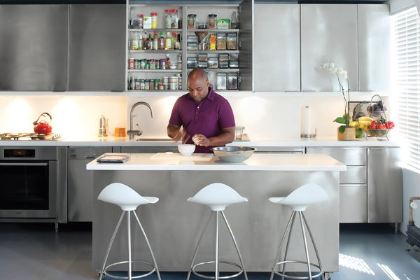 """The former dining room is now home to Russell and Fontanez's custom kitchen, designed by LOT-EK and fabricated by Chef Restaurant Supplies. """"We love to entertain,"""" Russell says. """"Before, the galley kitchen was in the hallway; now we can cook and still be a part of the party."""" The space-saving setup, which adjoins the living room, features stainless steel–paneled cabinets, DuPont Corian countertops, Onda stools by Jesus Gasca for Stua, and fixtures and appliances by Grohe, Liebherr, and Miele.  To maximize space, the designers specified that the cabinets be built around a former fireplace in the kitchen. """"Because there's a bump out where the chimney is, we turned the sink lengthwise,"""" Lignano says. """"The cabinet directly overhead is only four inches deep, so it's just a huge spice rack."""" The island provides ample additional storage."""