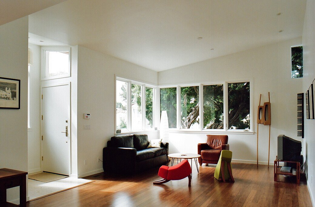 """The interior is brightly illuminated via the numerous low-e glazed windows by Marvin. They're thermally insulating and also help reduce noise from the neighboring BART track. One detail I really loved was the small corner window in the upper right of the photo, which faces west and allows the residents to view the setting sun in the evenings.  """"Maintaining sight lines throughout the house was really important to us,"""" says Ian.  The red and green chairs (whose forms are abstracted dogs) in the foreground are custom-built by Oakland-based furniture maker   Ashley Eriksmoen.  Building Green in Albany by Diana Budds"""