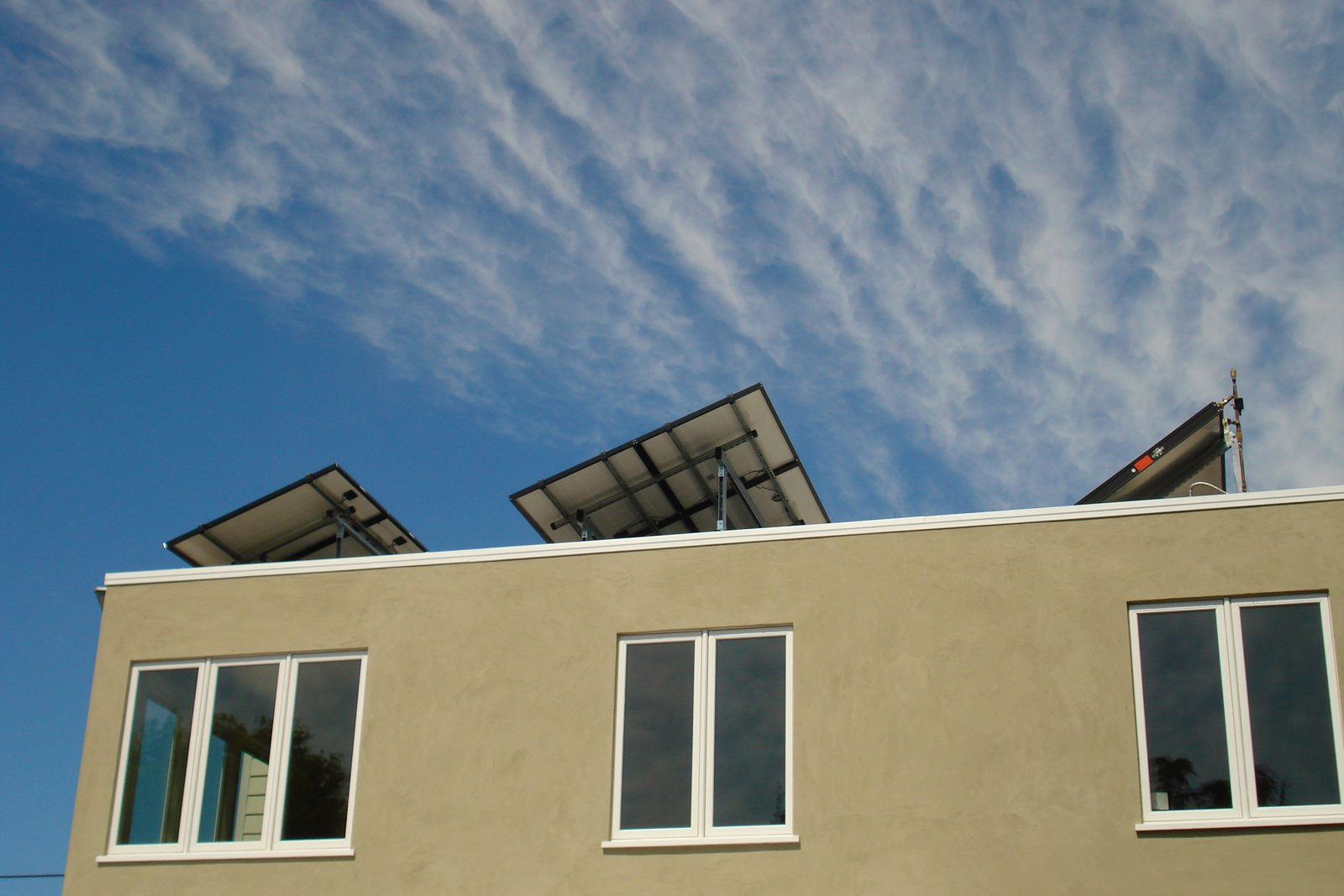 One of the main additions to the home was the rooftop solar hot water and 2.1 kW energy system, shown here from the rear of the house. The system is by Heliodyne.  Building Green in Albany by Diana Budds