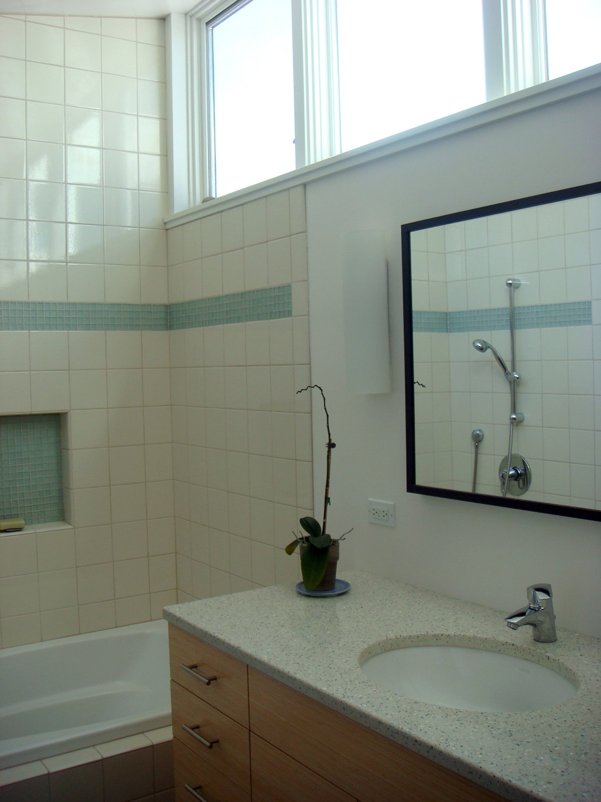 The bathroom features recycled countertops by IceStone. The low-flow sink faucet and the Croma E 75 shower fixture (visible in the mirror) are by HansGrohe. The tile in the shower is by Horus.  Building Green in Albany by Diana Budds