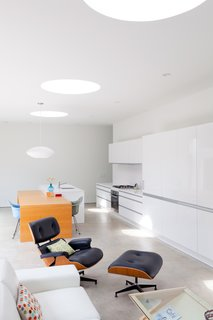 Though loads of natural light comes in from the courtyard, these large skylights also afford a view of the sky. The coffee table is from Modernica and the Eames Lounge is from Herman Miller.