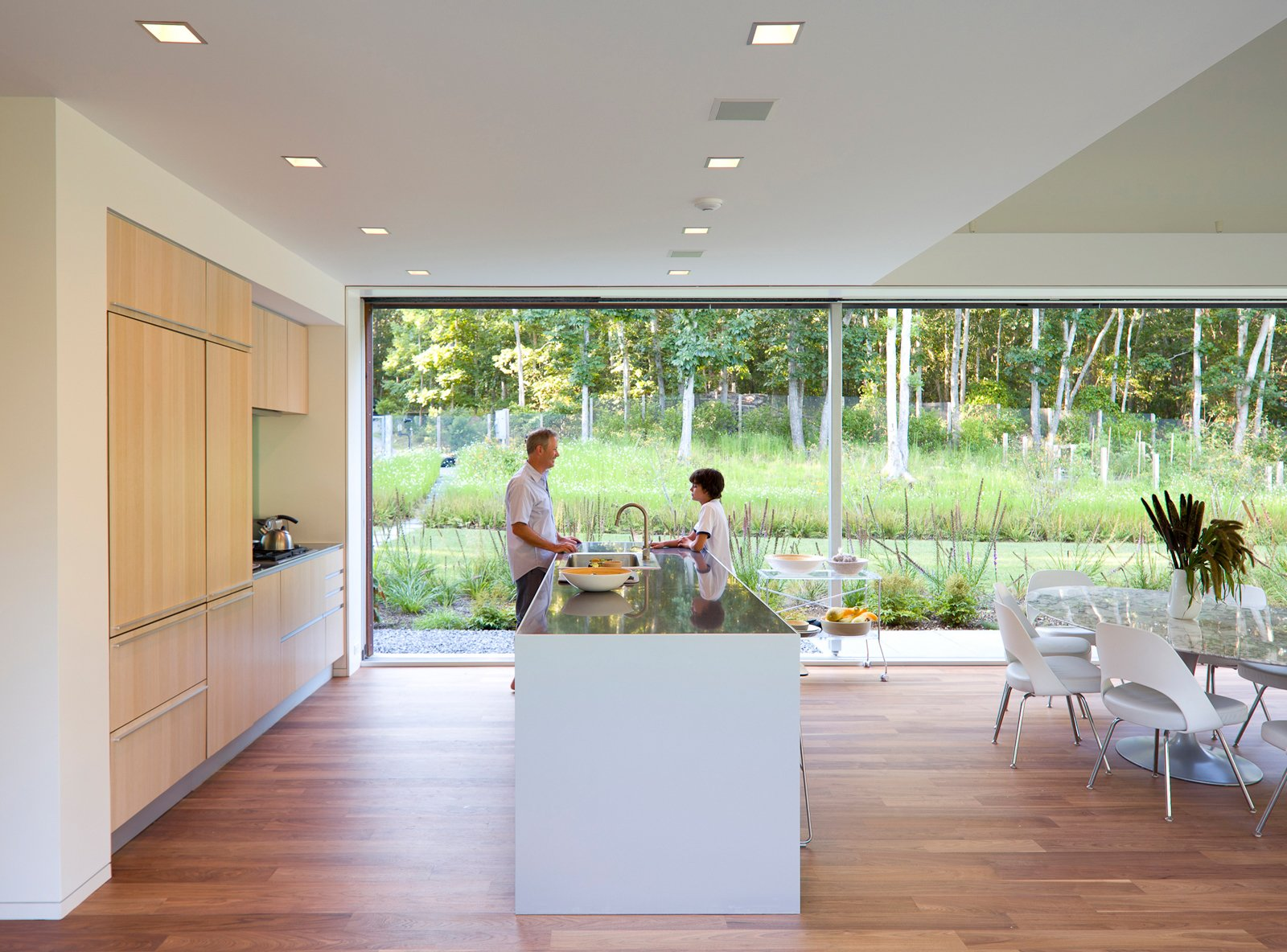 "Kitchen, Recessed Lighting, Medium Hardwood Floor, Drop In Sink, Range, and Wood Cabinet A double-height space encompasses the kitchen, dining and living area, and features 36-feet-wide glass doors that pocket into southern and northern walls.  Search ""7 small spaces incredible kitchens"" from Green Sustainable Home in Montauk"