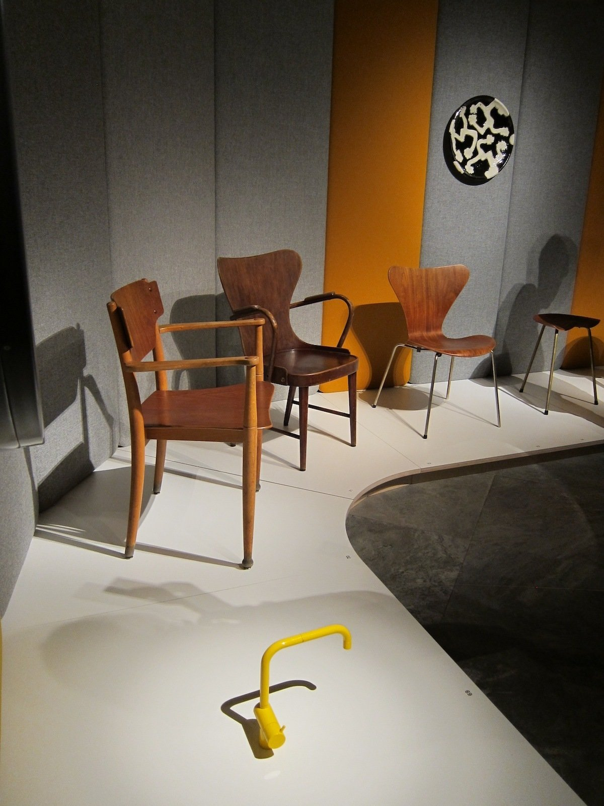 In one corner of the show, a bright yellow Vola faucet, designed by Arne Jacobsen and Teit Weylandt in 1969, holds court with a tribe of wooden chairs from the 1940s and 50s.  Photo 17 of 24 in A Cherner Chair Retrospective from Danish Design, Curated by Morrison