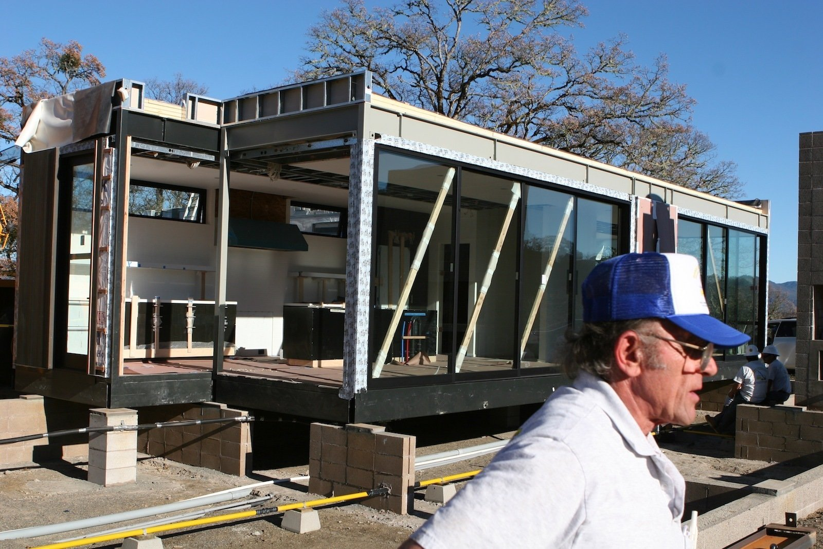 "After the kitchen modules are set in place, the diagonal bracing used during the transportation remains. ""The guy in the foreground worked for Marmol Radziner and had set pre-fabricated buildings all over the world during his career,"" says Bill. ""He was quite the cheerleader for the day and very good at this complicated process.""  Building a Prefab House by Jaime Gillin"