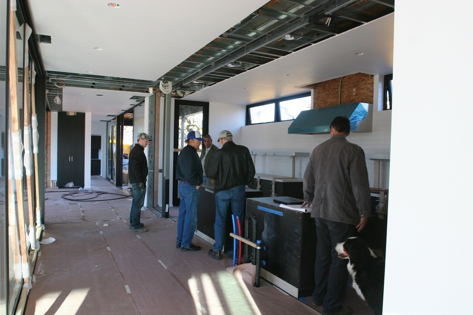 """At the end of the day, Abbie, Stella and some of the Marmol Radziner staff gathered in the kitchen. """"You can see the range hood in the background, the white tiled back wall of the kitchen, and seam in the ceiling where the two modules are joined,"""" says Bill.  Building a Prefab House by Jaime Gillin"""