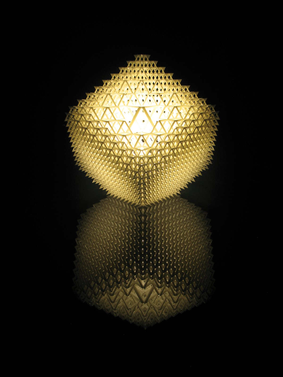 """Shine a Light  Benshetrit's table lamp, for the lighting and furniture company .MGX by Materialise uses QuaDror's infinitely scalable geometry to create a honeycomb of 1,200 modules that fits over a metal base holding a 40-watt halogen bulb. The lamp, which arrives   flat and expands, accordion-like, when lifted, is manufactured via selective laser sintering (SLS), a 3-D printing process that uses a laser to solidify layer upon layer   of powdered resin particles. """"When you   buy the lamp, you get a disc with the file   on it, so if it breaks, you can 'reprint' it,"""" Benshetrit says.  Search """"f k a table lamp"""" from Top Dror"""