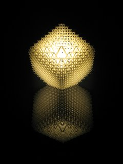 "Shine a Light  Benshetrit's table lamp, for the lighting and furniture company .MGX by Materialise uses QuaDror's infinitely scalable geometry to create a honeycomb of 1,200 modules that fits over a metal base holding a 40-watt halogen bulb. The lamp, which arrives   flat and expands, accordion-like, when lifted, is manufactured via selective laser sintering (SLS), a 3-D printing process that uses a laser to solidify layer upon layer   of powdered resin particles. ""When you   buy the lamp, you get a disc with the file   on it, so if it breaks, you can 'reprint' it,"" Benshetrit says."