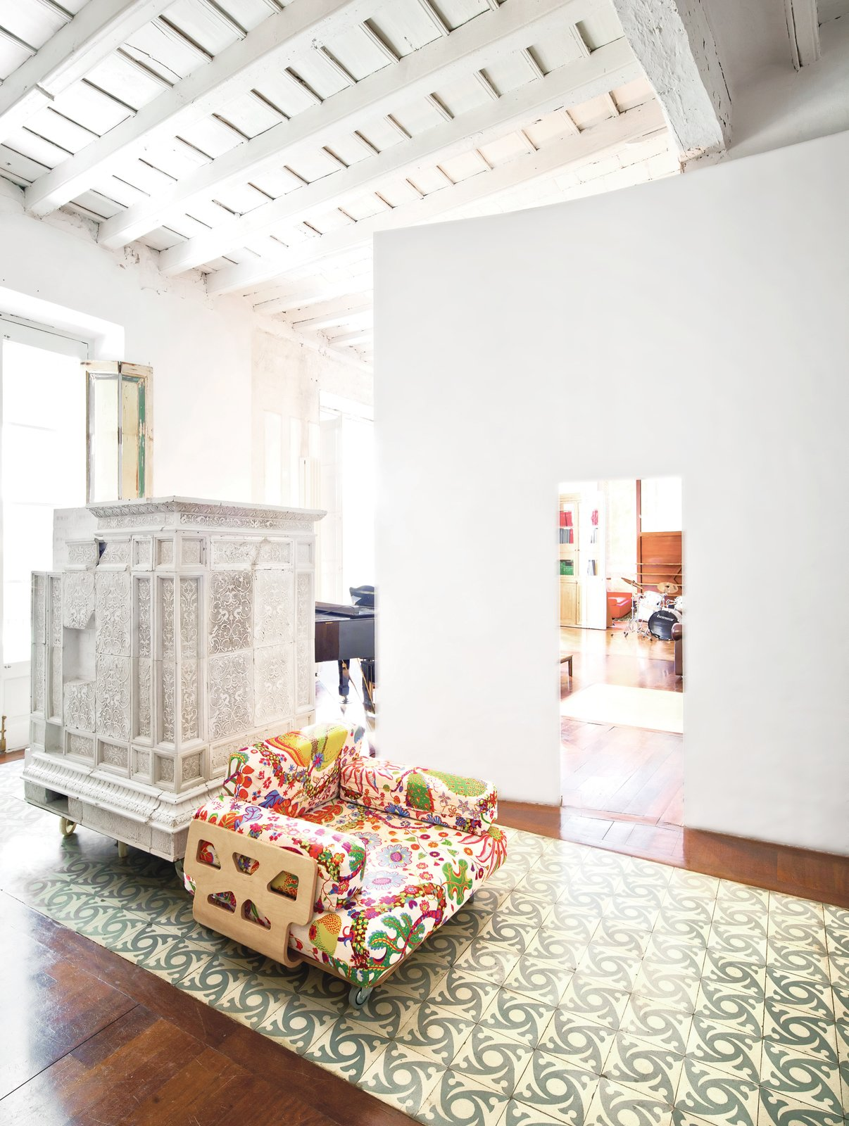 Living Room Paths of Andalusian tile and intervening plaster walls help to delineate space in the expansive apartment, which is centered around an internal entry courtyard. The armchair, designed by Peter and Alison Smithson, is covered in a Josef Frank textile from Just Scandinavian. The white piece just behind it is a repurposed Austrian stove that's now used as a storage device.  Photo 8 of 23 in The Barcelona Home Like No Other
