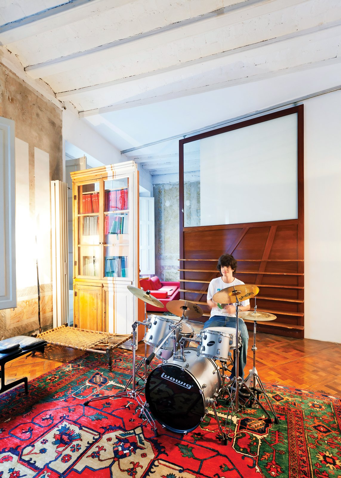 Kids Room In one area of the apartment, Tagliabue's son, Domenec, plays drums in front of a sliding wood panel of the architects' design.  Photo 9 of 23 in The Barcelona Home Like No Other