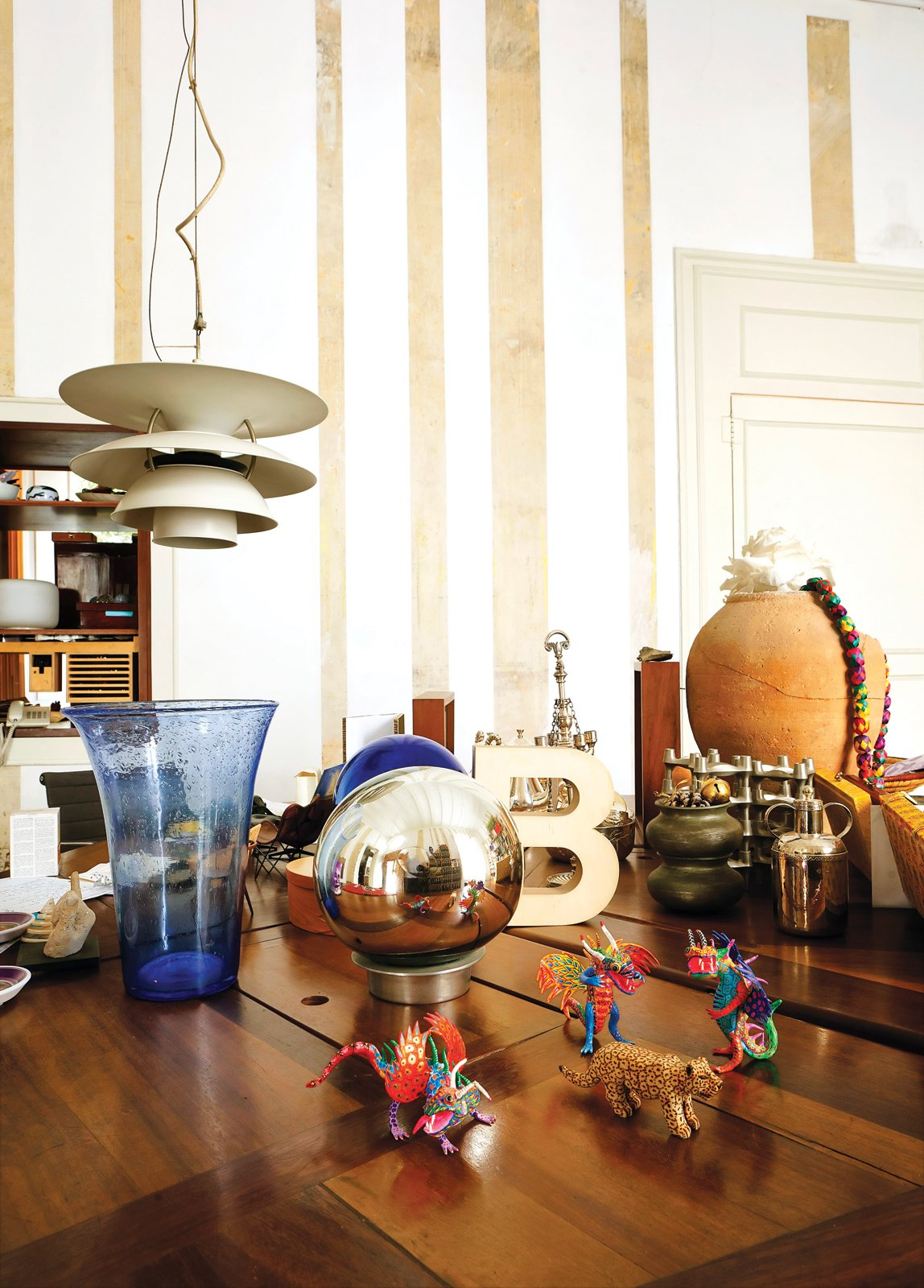 "Resting atop an oak table by Miralles, amidst a collection of tchotchkes, is the ""B"" trophy awarded to the pair for their work on the Santa Caterina Market rehabilitation project. A Louis Poulsen lamp hangs just above.  Photo 10 of 23 in The Barcelona Home Like No Other"