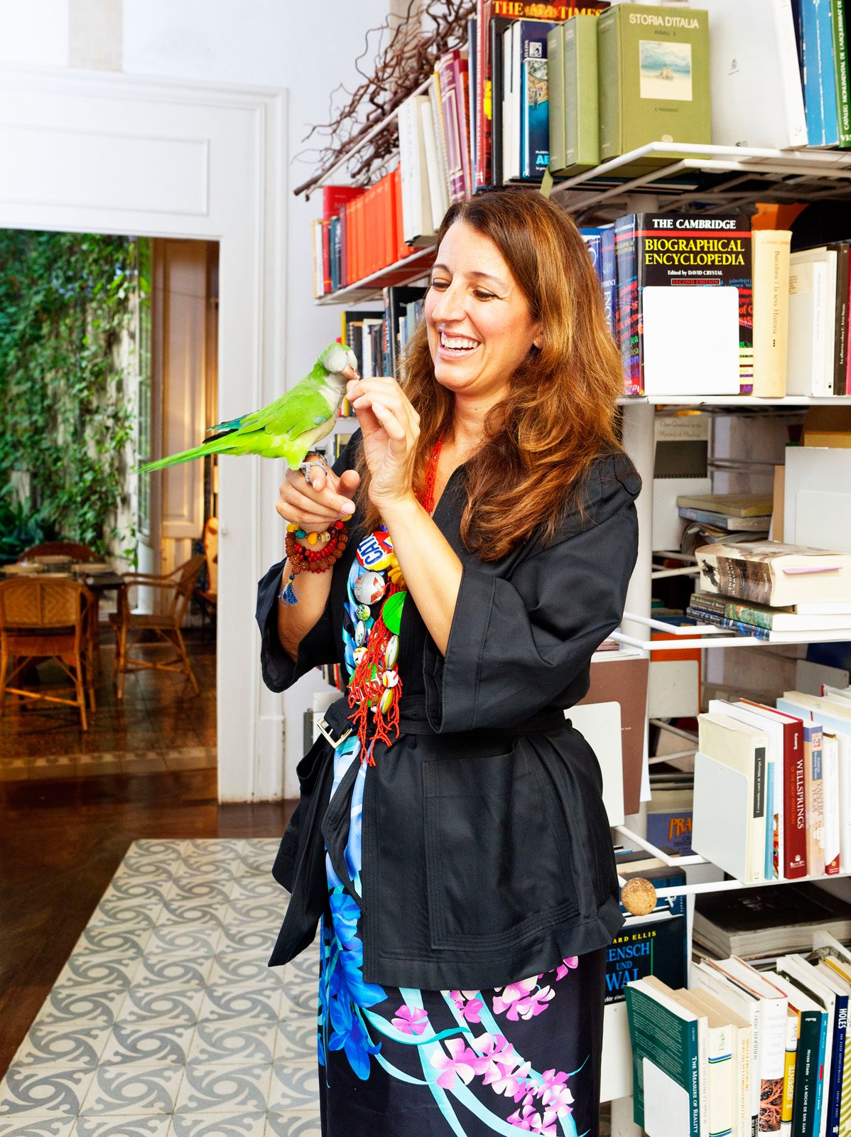 Office, Shelves, Library Room Type, Bookcase, Dark Hardwood Floor, and Rug Floor Benedetta poses with her pet bird, who keeps watch on the entrance courtyard below from his perch in the library.  Photo 22 of 23 in The Barcelona Home Like No Other