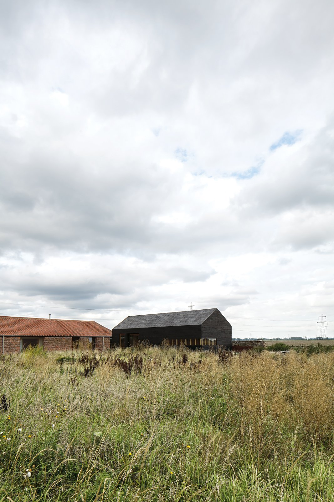 """Exterior and House Building Type Tucked away in a corner of Norfolk County, England, this pair of barns—one new, one renovated—sit low in the vast countryside.  Search """"mvrdvs balancing barn"""""""" from A Pair of English Barns Hide Unabashedly Bold and Budget-Friendly Minimalist Interiors"""