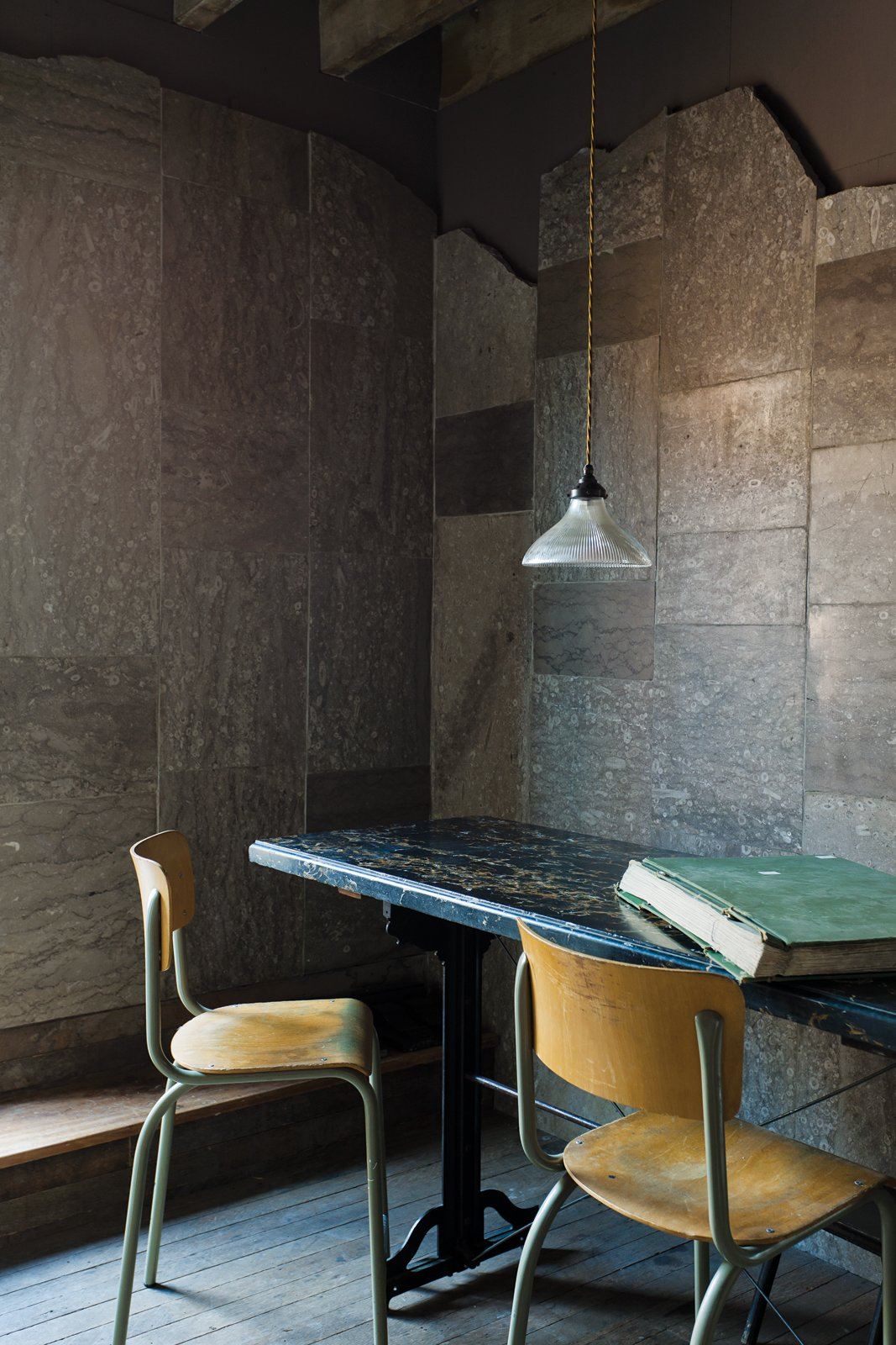 Dining Room, Table, Chair, and Pendant Lighting In a corner of the warehouse, the Heathrow limestone clads the walls.  Photo 3 of 3 in Protect and Conserve