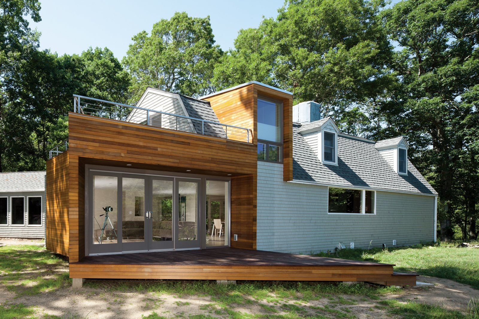 """Exterior, House Building Type, Wood Siding Material, and Shingles Roof Material Creative Direction  The arrowhead-shaped corner at the end of the living room evolved from the need to accommodate a standard sliding-glass-door module. """"It would have been astronomically expensive to custom-build it,"""" says Chris Bardt. This architectural gesture—  the arrow """"points"""" toward the river—""""enabled us to be very generous with the view area without having to extend the entire house.""""  Best Photos from New McDonald"""