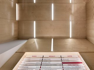 Horizontal lights are interspersed throughout the folded geometric plane of the ceiling.