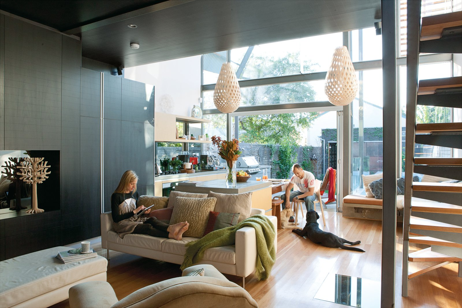 Living Room, Sofa, Pendant Lighting, Light Hardwood Floor, Chair, Ottomans, and Bench Brammy and Kyprianou hung Koura pendant lights by New Zealand designer David Trubridge above the dining area. Their organic forms and diamond-shaped shadows create intimacy in the vast space. Among Bilardo's contributions were the black tulipwood cabinetry and ceiling and the cantilevered concrete countertop that appears to go through the glass wall.  Photo 3 of 9 in This Luminous Australian Renovation Packs a Lot Into a 23-Foot-Wide Lot