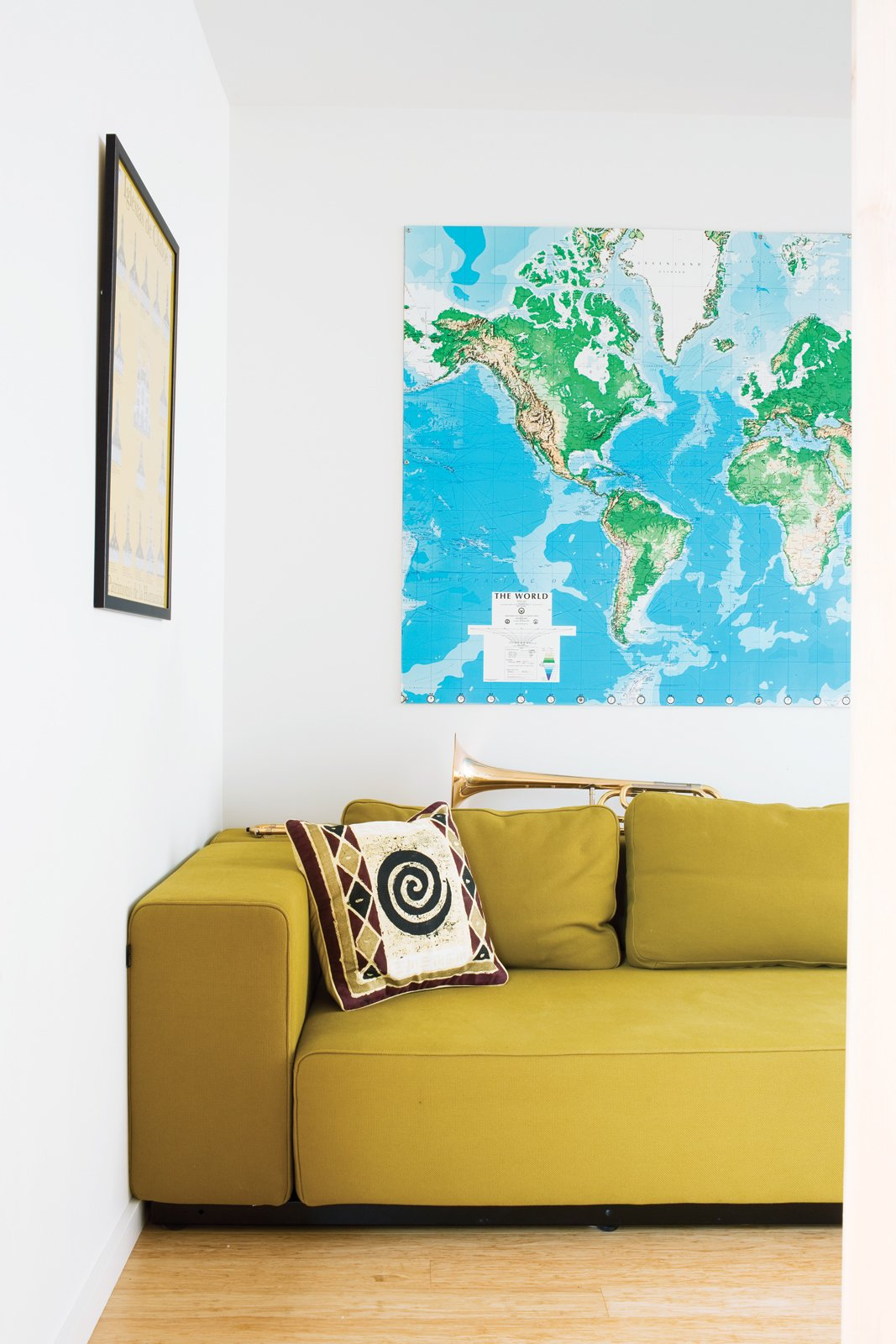 A mustardy couch and a large map of the world—Whitlock travels all over the place for work—keep the living room bright and cheerful. Tagged: Living Room, Sofa, and Light Hardwood Floor.  Photo 9 of 16 in A Sound Professional Goes DIY While Building an Affordable Montana Home