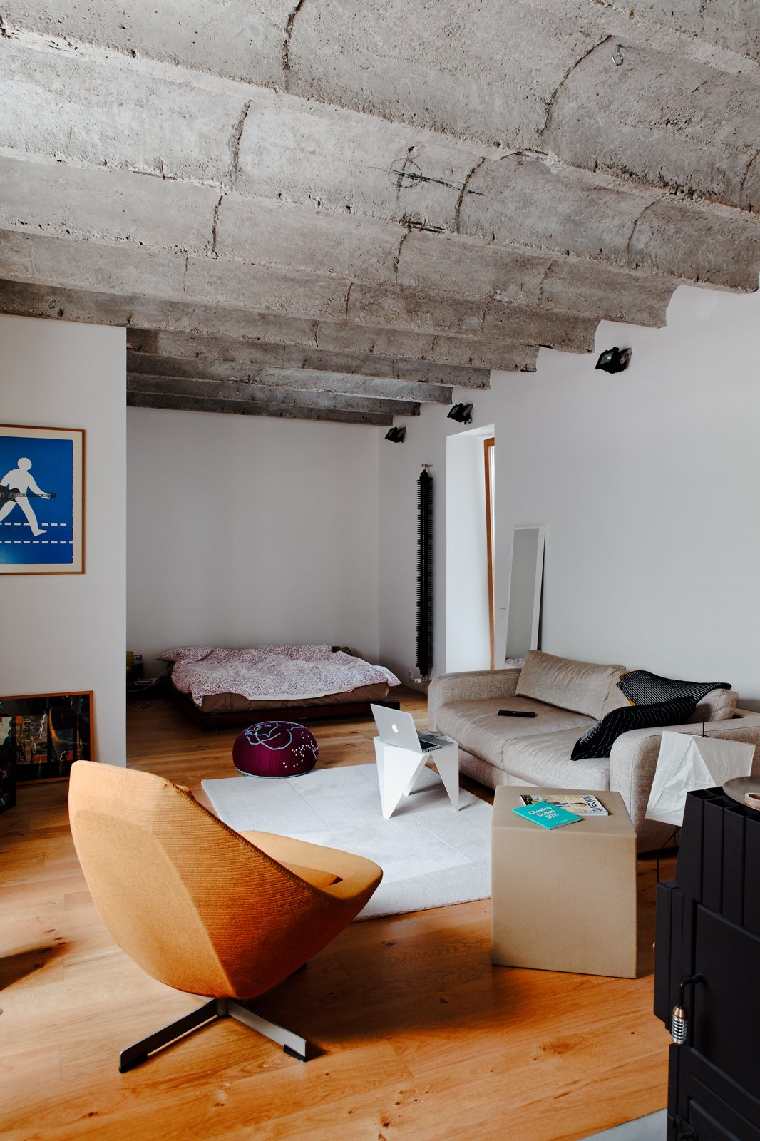 The rest of Kordík's small apartment is given over to an open-plan living and bedroom. The waves of the concrete ceiling offer a bit of overhead character while lounging on the couch or in bed.  Photo 3 of 8 in A Little Apartment Gets a Solid Renovation