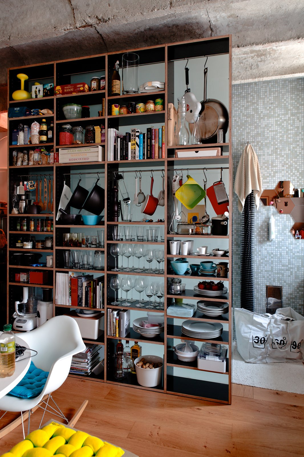 """Kordík uses his cabinet system to store far more than just dishes. Food, kitchen appliances, and books also hold court in the dining area. We love that the three volumes of Julius Shulman: Modernism Rediscovered live right beneath jars of snacks.  Search """"7 small spaces incredible kitchens"""" from A Little Apartment Gets a Solid Renovation"""
