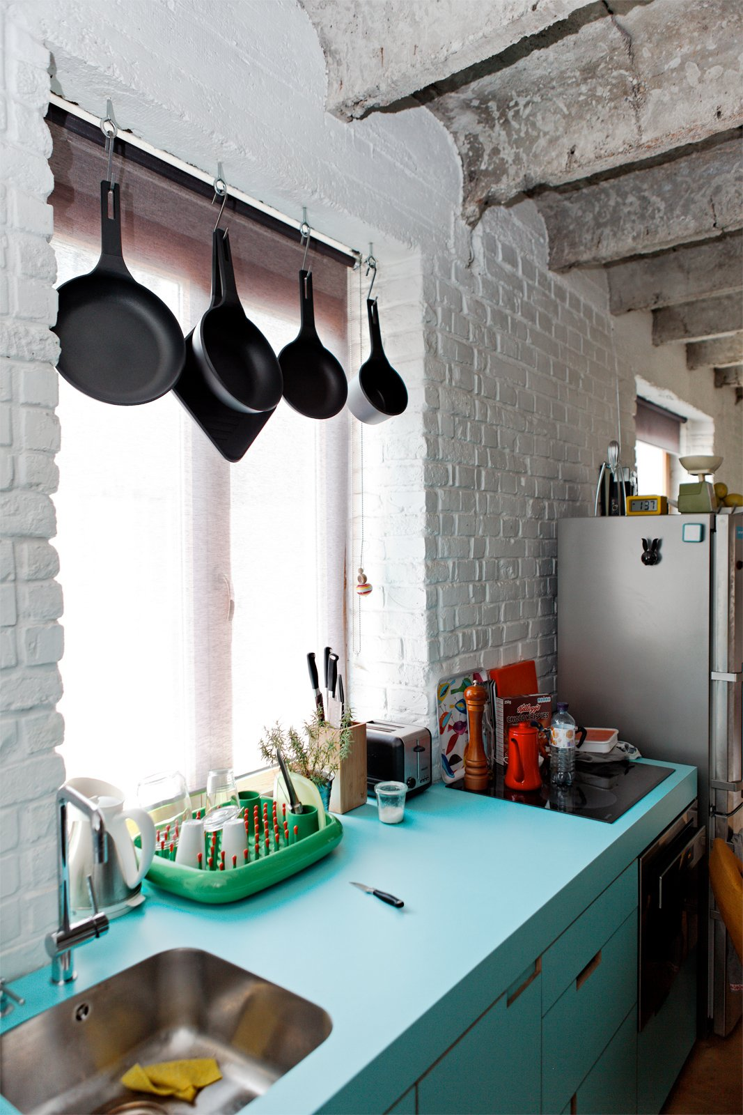"""A green Dish Doctor by Marc Newson for Magis adds just a bit more color to the blue facing of the kitchen sink and cabinets.  Search """"7 small spaces incredible kitchens"""" from A Little Apartment Gets a Solid Renovation"""