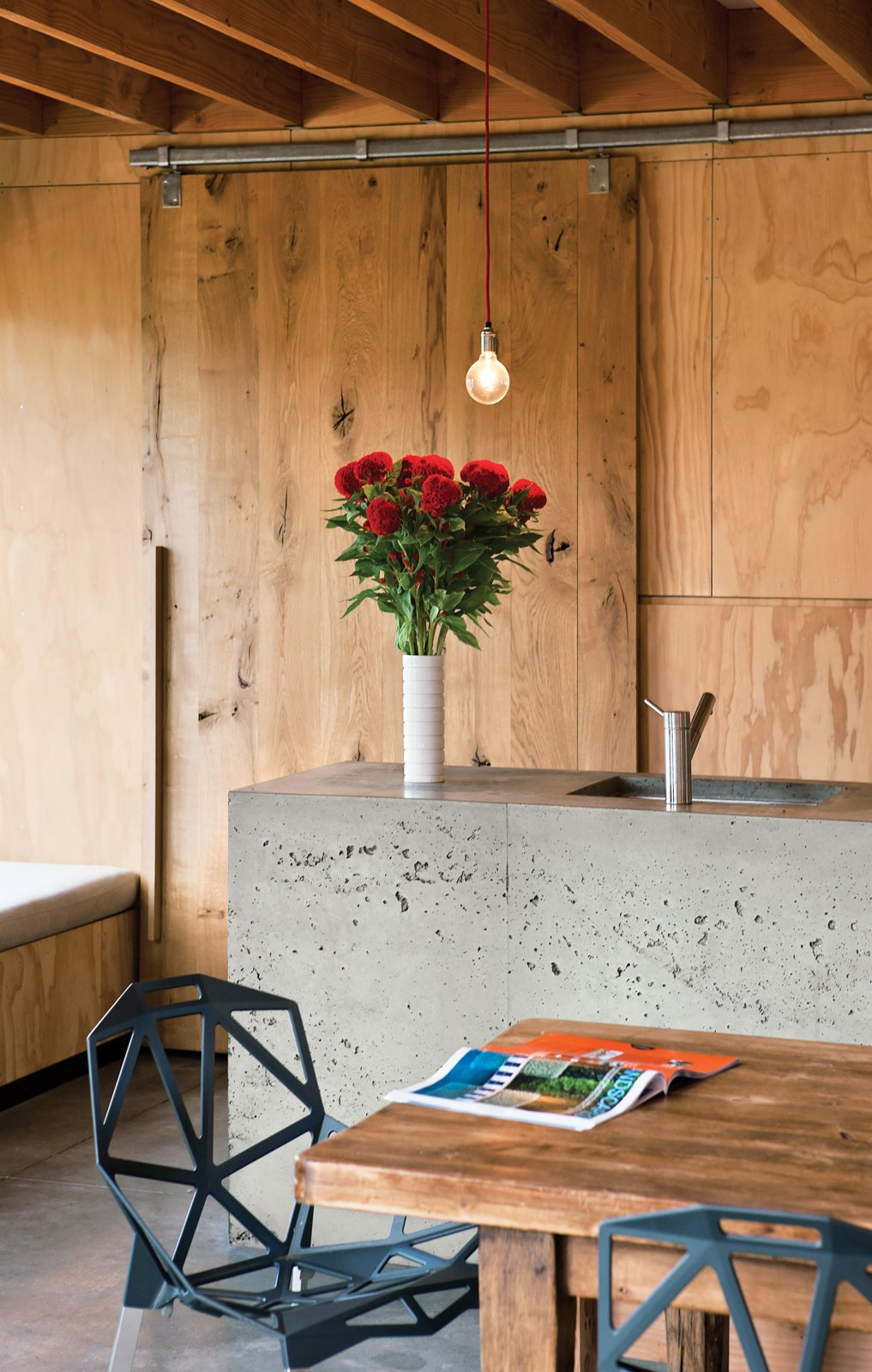 Kitchen, Concrete Counter, Pendant Lighting, Concrete Floor, Wood Cabinet, Wood Backsplashe, and Undermount Sink Island Life  The appealing, handcrafted appearance of the concrete kitchen island is a happy accident, the result of the concrete not settling fully in its timber framing. When the framing was   removed, the builder, Peter Davidson, was worried that Davor and Abbe would be disappointed with the bubbled result and offered to start the process again, but they loved its one-off feeling and persuaded him to keep it that way.  Photo 3 of 20 in How to Recognize Different Wood Species: A Guide to the 10 Most Common Types from Rock the Boat