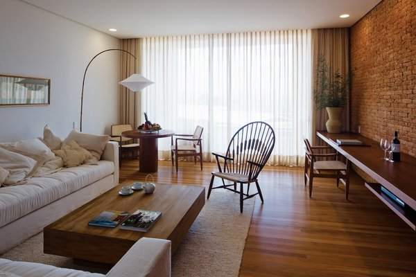 The suites are all duplexes, with one room upstairs and another below. The chair is called the Oscar, also designed by Sergio Rodrigues, and the workstation is crafted from Brazilian jacaranda wood.