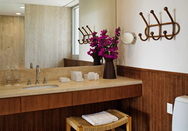 The bathroom features a Duravit sink and gorgeous Brazilian wood paneling. The metal jar and wooden stool are from local designers.