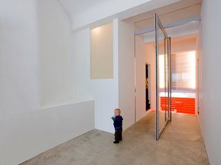 The home's different levels create a playful experience for the inhabitants. The concrete floor references the building's past use as a garage for ambulances.