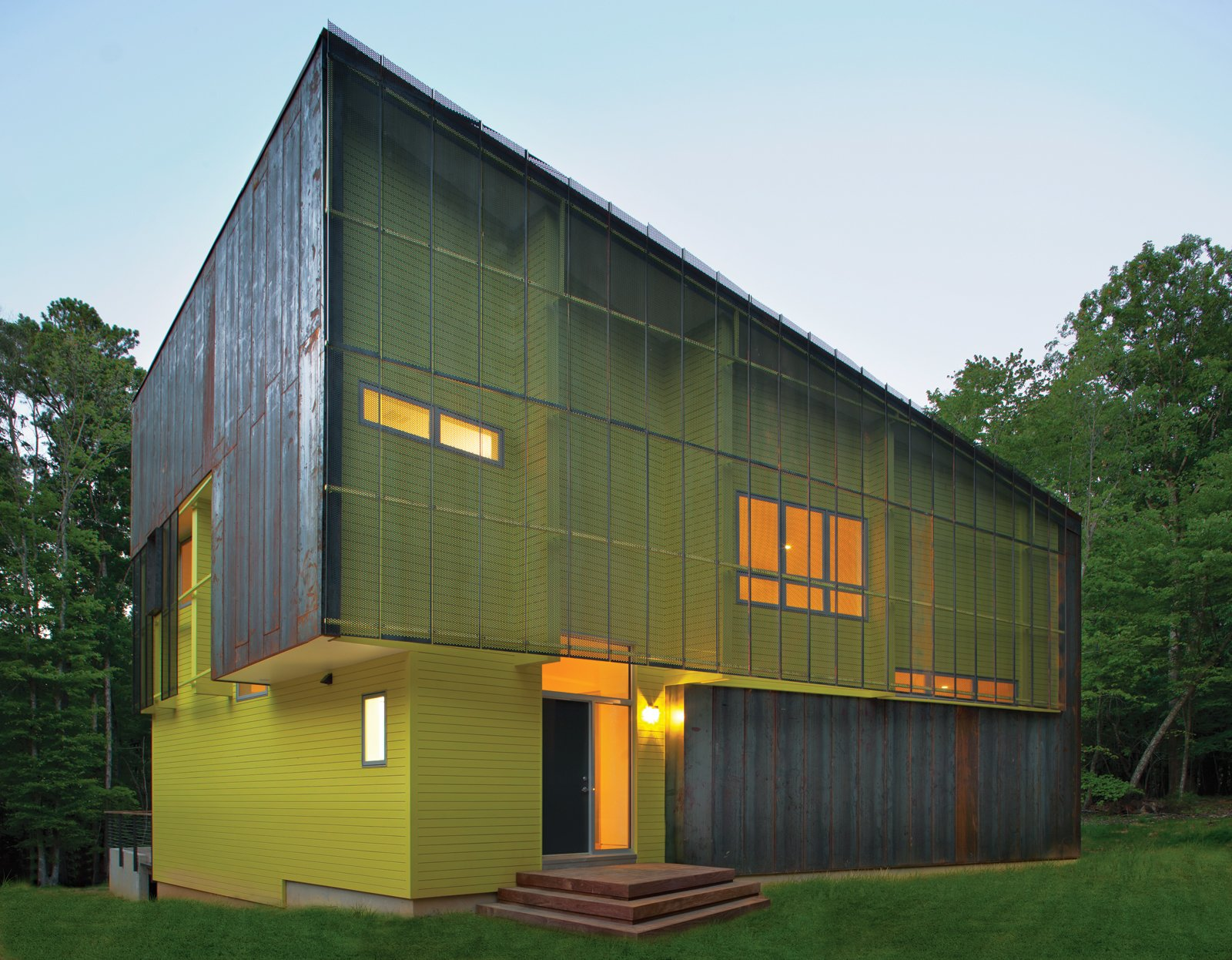 Exterior, Metal Roof Material, House Building Type, Wood Siding Material, Metal Siding Material, and Shed RoofLine Tuned into its sylvan setting, this affordable green home in Hillsborough, North Carolina, is a modern take on the surrounding centuries-old structures. The bright green paint on its facade contrasts with the Cor-Ten steel cladding.  Photo 1 of 2 in Region of Honor