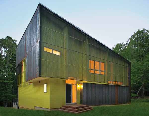 Tuned into its sylvan setting, this affordable green home in Hillsborough, North Carolina, is a modern take on the surrounding centuries-old structures. The bright green paint on its facade contrasts with the Cor-Ten steel cladding.