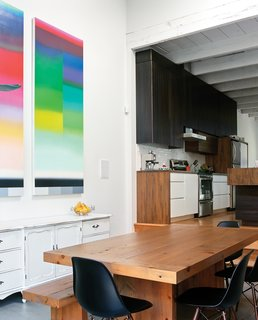 The architect designed the kitchen cabinetry, and used wood left over from the demo of the house's exterior wall for the dining table. A piece by Nicolas Grenier hangs above a cabinet the residents found at a garage sale.