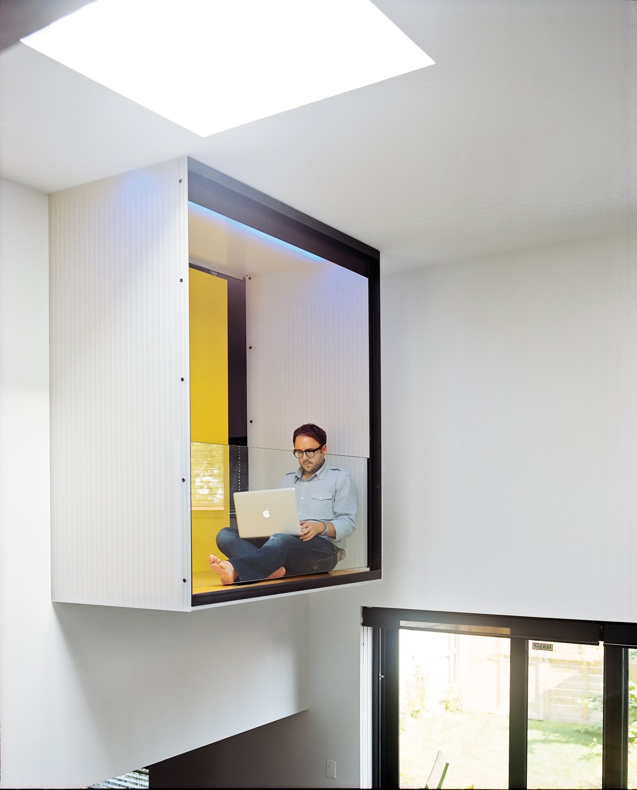 Raymond takes a break on the master bedroom's interior balcony, which is cantilevered over the dining area. Tagged: Windows and Skylight Window Type.  A Look at Reading Nooks by Diana Budds from Split the Difference