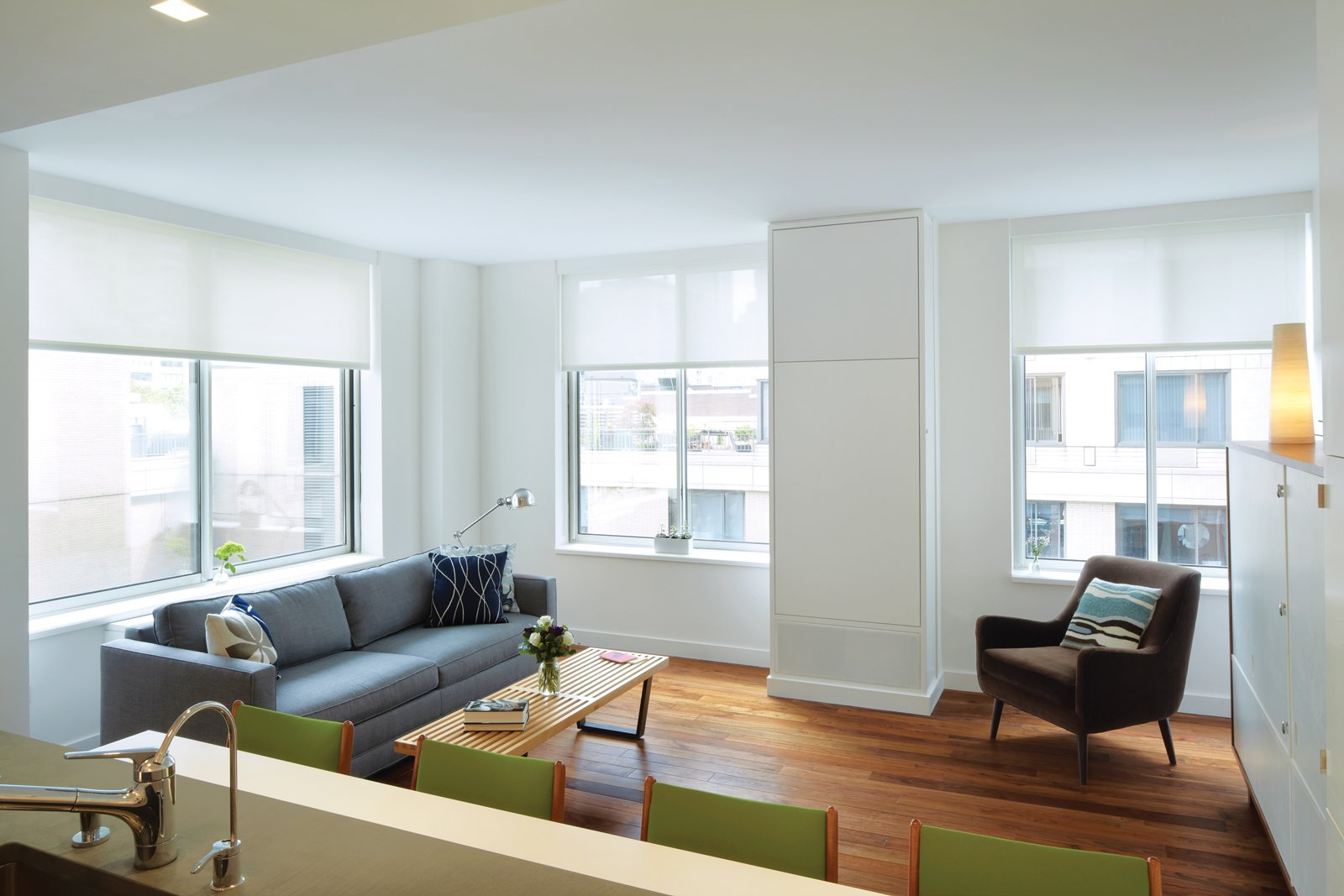 Living Room, Medium Hardwood Floor, Sofa, Chair, Lamps, Coffee Tables, Storage, Recessed Lighting, Table Lighting, Stools, and Bar Like a Murphy bed, the dining table tucks into the wall when not in use.  Photo 3 of 11 in These 10 Tiny Apartments in New York City Embrace Compact Living from Hide and Eat