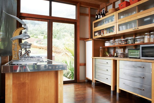 The kitchen occupies one corner of the L-shaped structure. As throughout, the floors are made up of reclaimed eucalyptus that Chris planed himself.