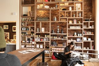 """Nemaworkshop has quite a few cafe projects under their belt. """"Owners are looking for us to develop spaces that are casual, comfortable, and not overly designed,"""" says Nema. """"They should feel relaxed and casual, carefully designed but seeming effortless."""" The shelving filled with coffee, team brewing equipment, and more for sale feels like more like a living-room bookshelf than selling space."""