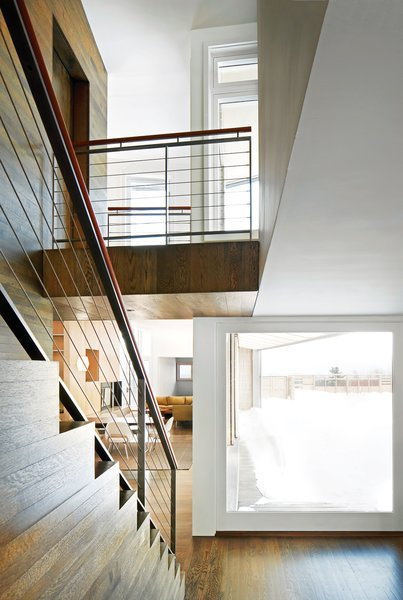 The house's L shape permits a considerable courtyard, and plenty of space for lounging behind the rain screen. The stairs sit at the intersection of the two volumes and lead down into the more social of the two: the dining room, living room, and music room.