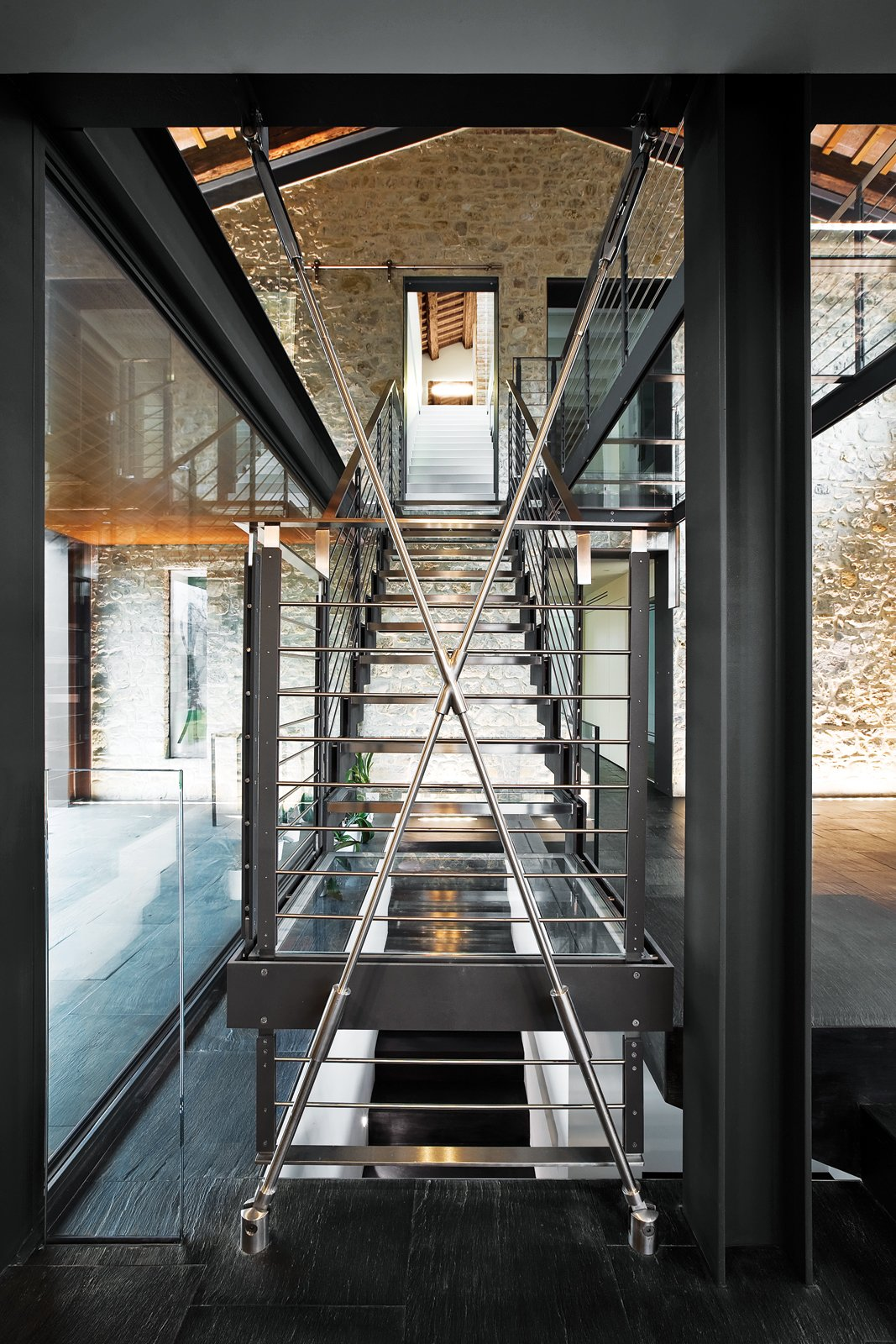 Staircase, Metal Railing, and Metal Tread Rising to a catwalk above, a huge glass-and-steel central stair envisioned by the architect spans four floors of the Chiavellis' newly expanded house.  190+ Best Modern Staircase Ideas from A Renovated Farmhouse in Northern Italy