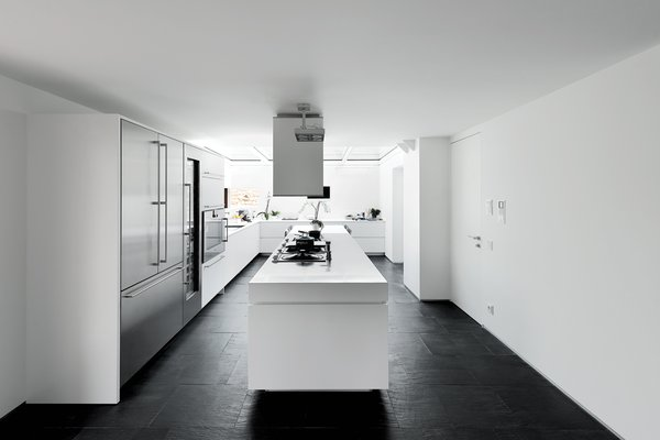 A massive white island range is anchored by locally sourced Italian slate floors in black. In this black and white kitchen, cabinets, countertops, and walls are finished in white so as to prevent the space from feeling too dark. To shed even more light, a glass ceiling at the far end of the kitchen presents an open-air feeling.