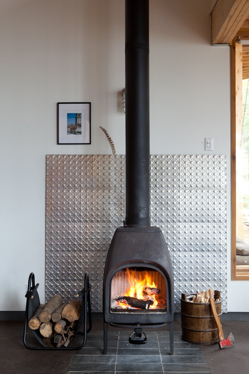 Living Room, Standard Layout Fireplace, and Wood Burning Fireplace The structures share a solar panel, but the families control their own home's heat level with a wood-burning stove.  Photo 9 of 14 in Four Friends Joined Forces to Realize This Idyllic Forest Retreat Outside Toronto