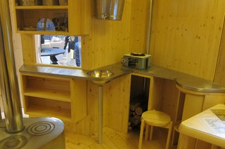 """The """"kitchen"""" is comprised of a stainless-steel worktop, a steel basin for melting snow, containers for staples, and a shelf for a camping stove."""
