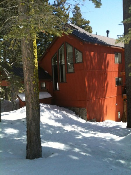 Amidst the brown natural tones of the surrounding cabins, this orange-red exterior pops. The contrasting charcoal trim and coordinated art in the window pull the whole thing together.  Cabin from Snow in Bear Valley