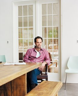 Tom Givone sits at a table of his own design, which   he had fabricated from reclaimed wood by a local carpenter.