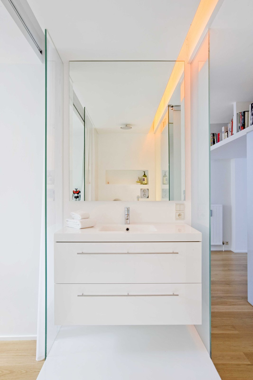 In an unconventional twist, the bathroom is separated into two rooms: a glass-walled shower/sink area shown here and a more private room for the toilet.  Casa H, Brussels by Diana Budds
