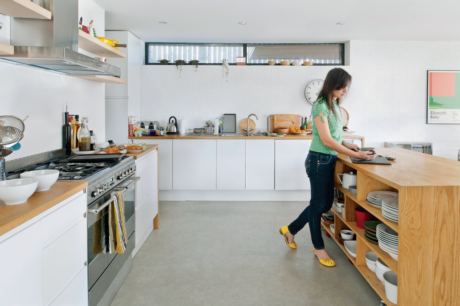 """Kitchen, Wood Counter, and White Cabinet About her collection of cookware, Tyler comments: """"I use accessories as the color in spaces so these items are an integral part of the overall design.""""  Photo 7 of 18 in An Obsessed Designer Fills Her Home with Vintage Finds"""