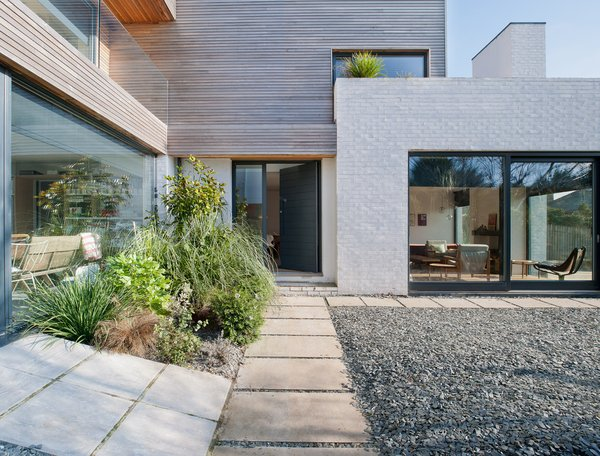 A path leads past glazing and gravel to the front door.