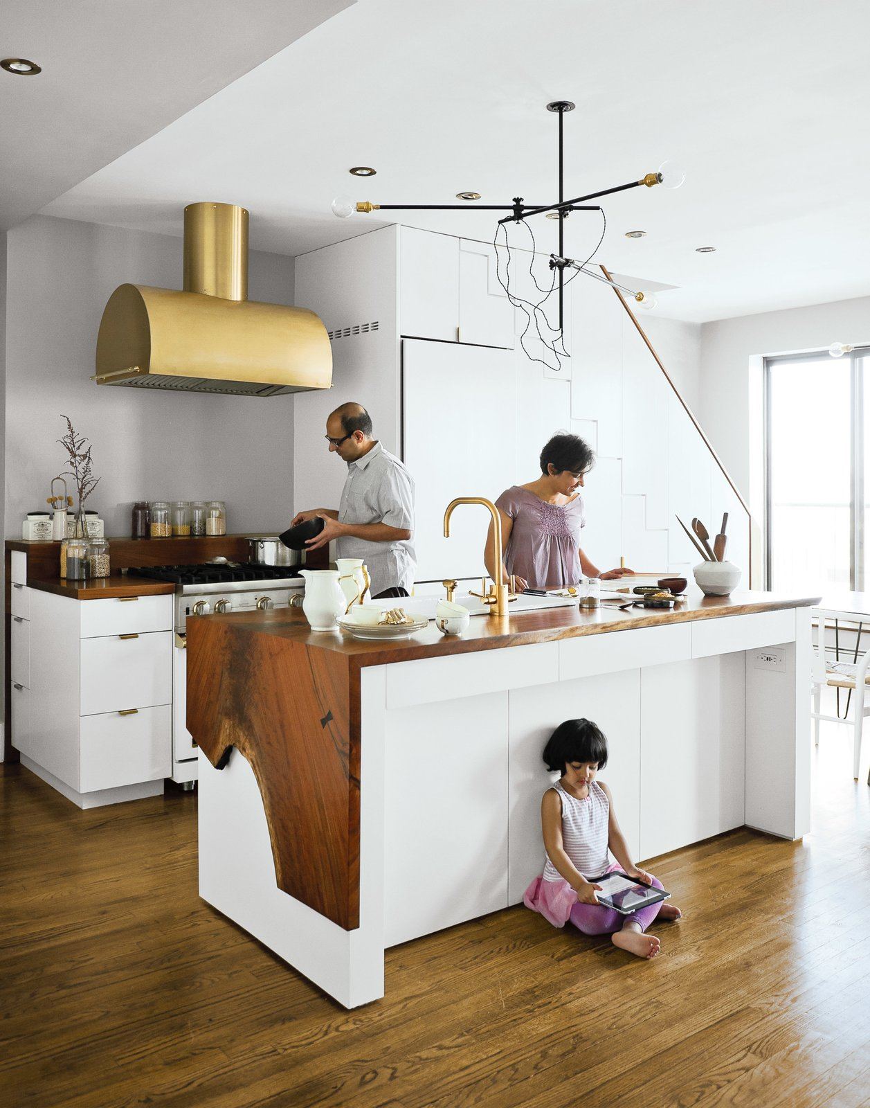 Kitchen, White, Medium Hardwood, Wood, Metal, Pendant, Range Hood, Range, Recessed, Wall Oven, and Vessel A couple takes a minimalist approach to their Brooklyn apartment, focusing on supple materials, subtle gradations of color, and custom finishes by local craftsmen. The Mandayam–Vohra family gathers under one of Workstead's signature three-arm chandeliers, shown here in its horizontal configuration. Bartenschlager designed the white cabinets and is responsible for the walnut counters both on the kitchen island and near the stove.    Best Kitchen Range Hood Wall Oven Metal Photos from A Minimal Yet Mighty Brooklyn Apartment