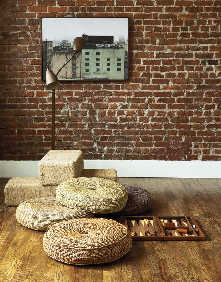 A couple takes a minimalist approach to their Brooklyn apartment, focusing on supple materials, subtle gradations of color, and custom finishes by local craftsmen. Exposed brick adds plenty of texture to the room.  Photo 4 of 12 in A Minimal Yet Mighty Brooklyn Apartment
