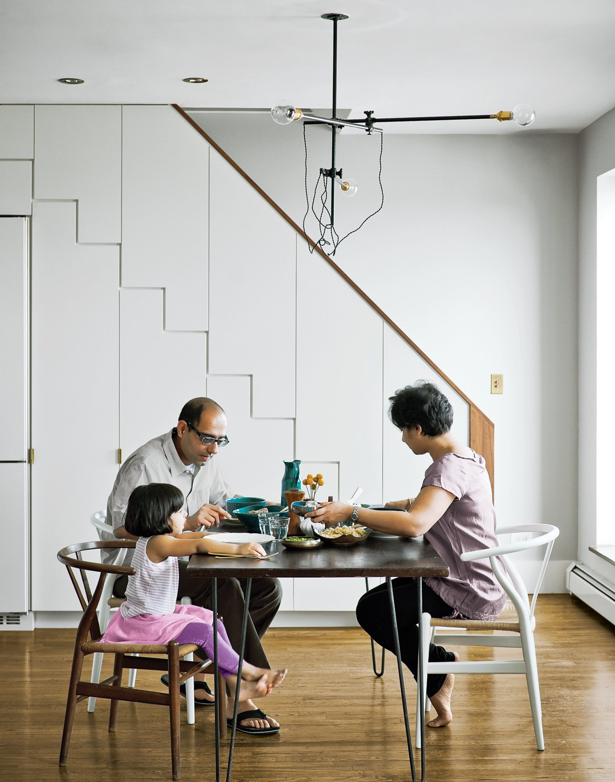 Staircase and Wood Railing At right, the family dines at a mid-century walnut table found on eBay,   seated at a mix of new and antique   Wishbone chairs by Hans Wegner.  Photo 1 of 12 in A Minimal Yet Mighty Brooklyn Apartment