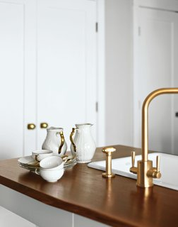 A Rohl faucet was stripped and replated in brushed brass. The modern fixtures prove a lovely contrast to the American walnut countertops and original Rosenthal dishware.