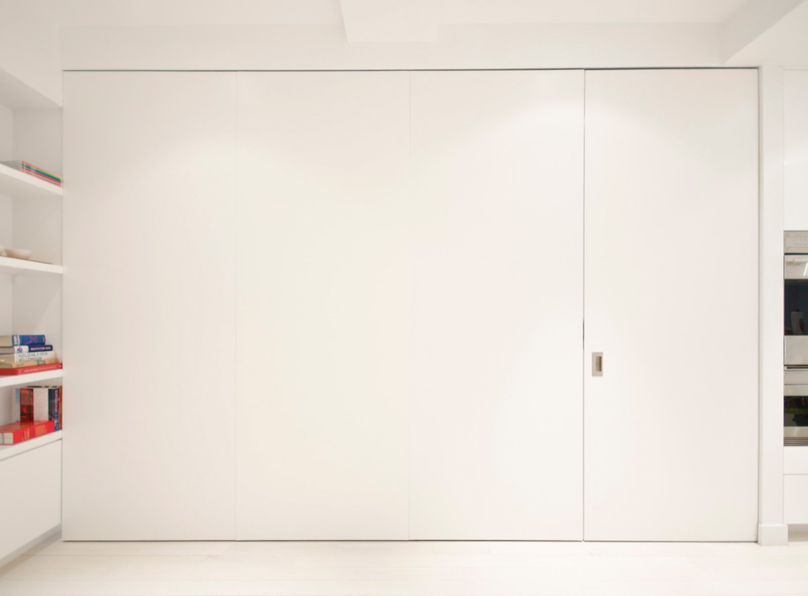 One of the home's boldest space-saving moves is this set of custom pivot-sliding doors, which offers the flexibility of a private room for guests without having to be permanently closed off from the rest of the apartment when not in use.  University Place Apartment by Diana Budds